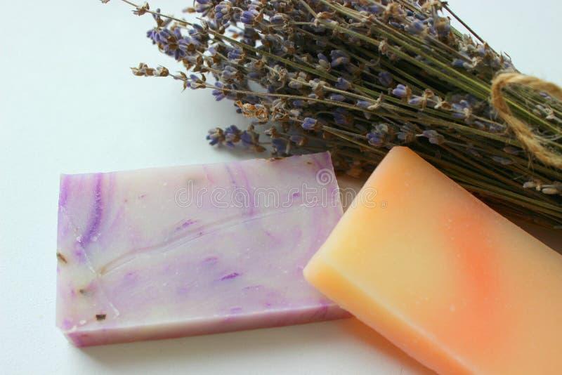手工制造肥皂几个片断和淡紫色花花束在白色背景的 免版税库存图片
