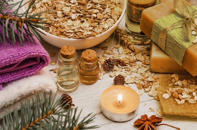手工制造肥皂和洗涤的油在白色土气木背景 蜂窝、燕麦和蜂蜜 自然有机化妆用品 温泉 免版税库存图片
