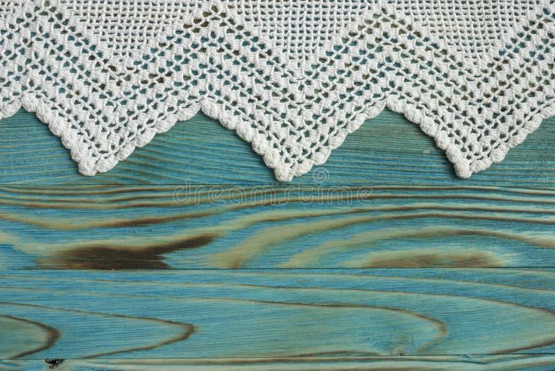 手工制造钩针编织的在木背景的棉花有机毯子 白色原始的钩针编织鞋带框架 免版税库存照片