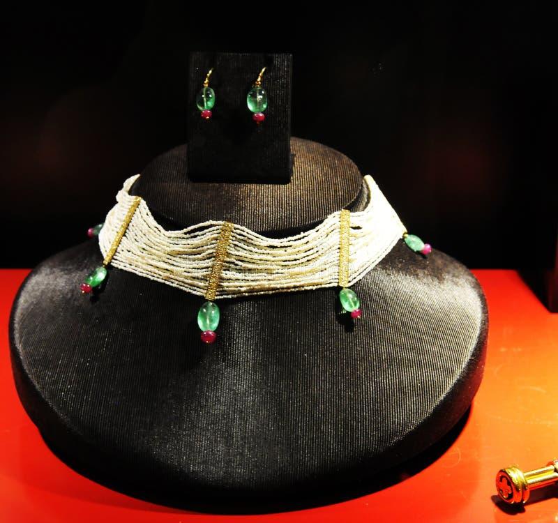 手工制造首饰片断-项链和耳环有珍珠,绿色和红色宝石的,宝石 图库摄影