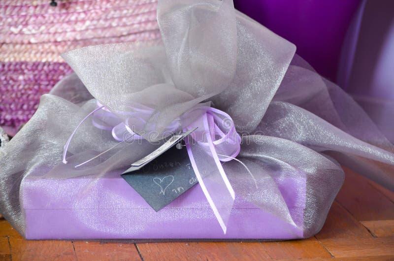 手工制造紫色礼物手写的卡片丝毫心脏和礼物在紫色背景 免版税图库摄影