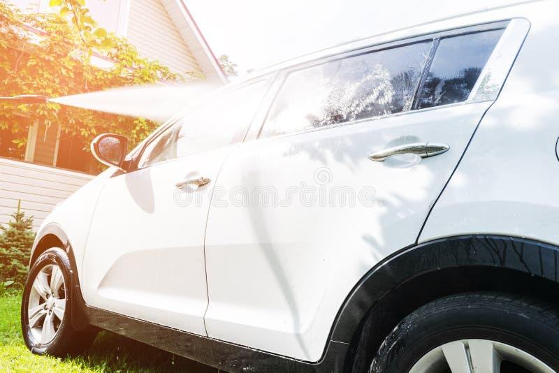 手工洗车用外面压力水 夏天汽车洗涤物 使用高压水的清洁汽车 汽车详述 手washe 库存图片