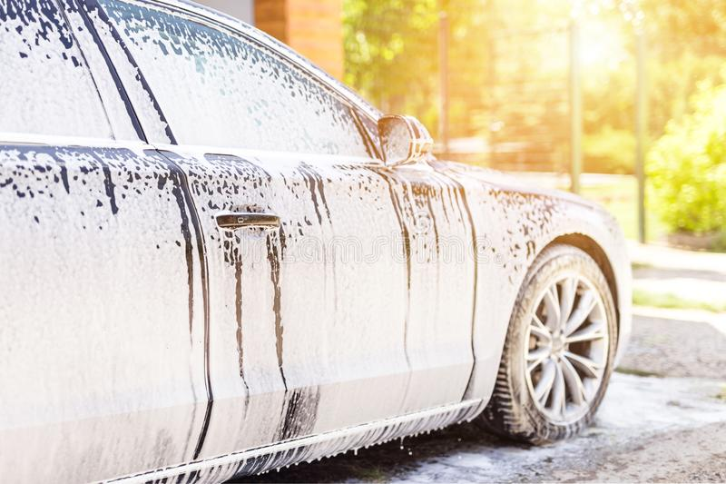 手工洗车 有白色泡沫似的洗涤剂的洗涤的豪华车 汽车清洁自已服务 图库摄影