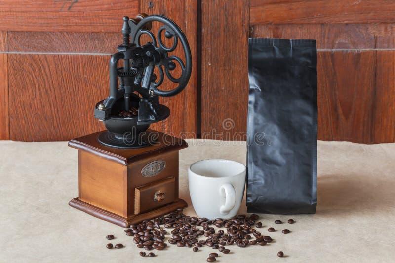 手工磨咖啡器用杯子咖啡和与咖啡袋的黑咖啡豆回收纸 免版税库存图片
