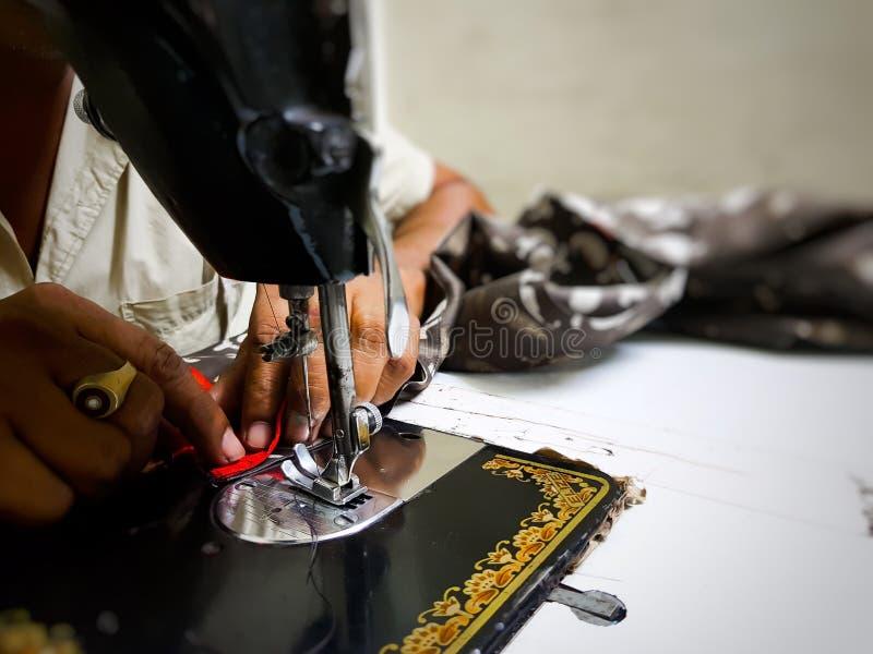 手工缝纫机接近的照片用缝与选择聚焦的裁缝手红色布料 图库摄影