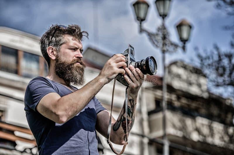 手工设置 摄影师举行葡萄酒照相机 现代博客作者 美满的创作者 人有胡子的行家摄影师 免版税库存照片