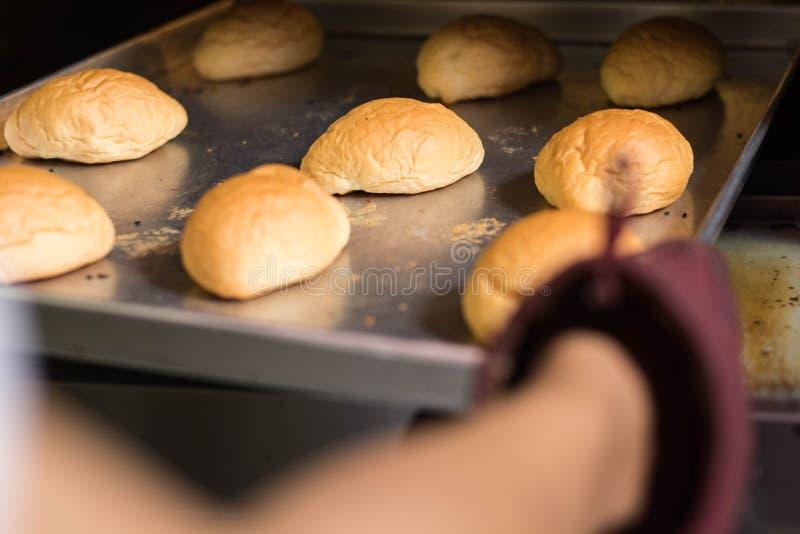 手徒升有厨房手套的从烤箱里边投入或采取面包 采取新鲜面包的手背面图 库存图片
