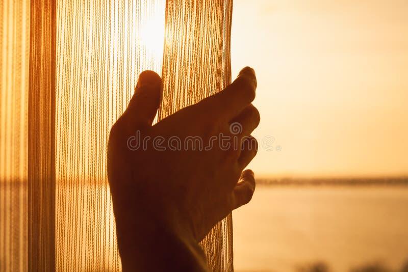 手打开窗口的薄纱与阳光 免版税库存照片
