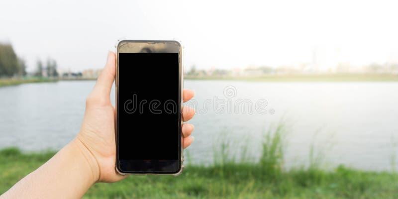 手扶的智能手机在公园 免版税库存图片