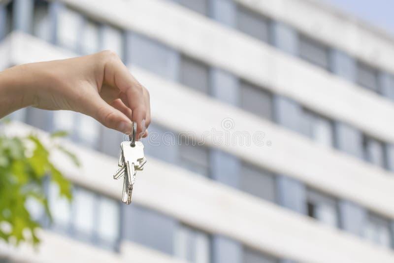 手把握关键对一栋被购买的公寓以一个多层的大厦为背景 库存照片
