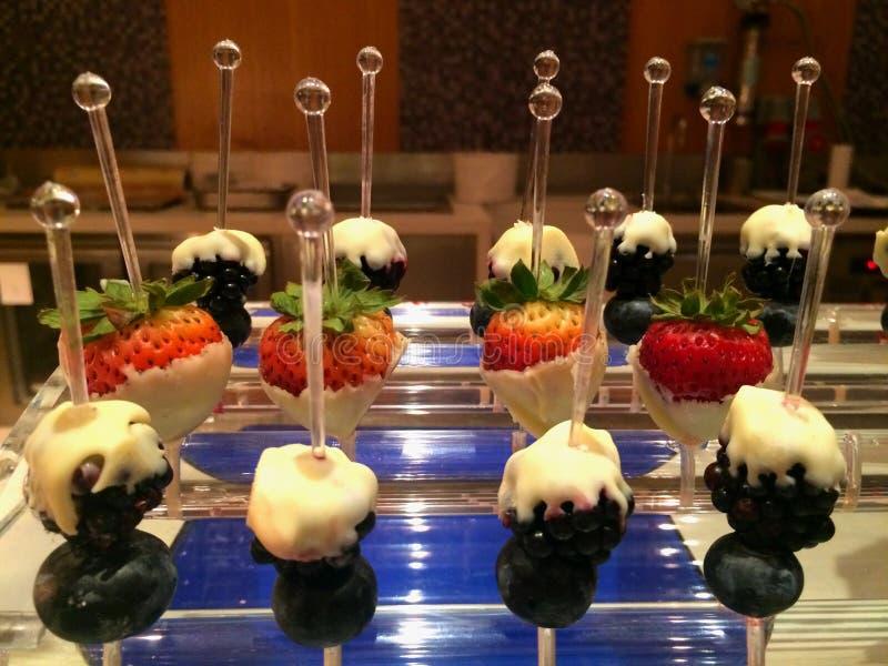 手抓食物、草莓和莓蘸白色巧克力 库存照片