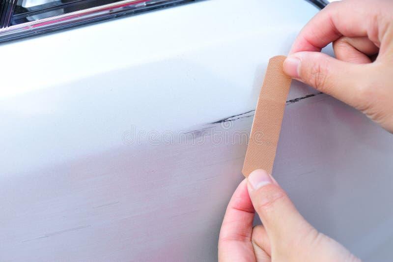 手投入了一块胶布在汽车抓痕 免版税库存图片