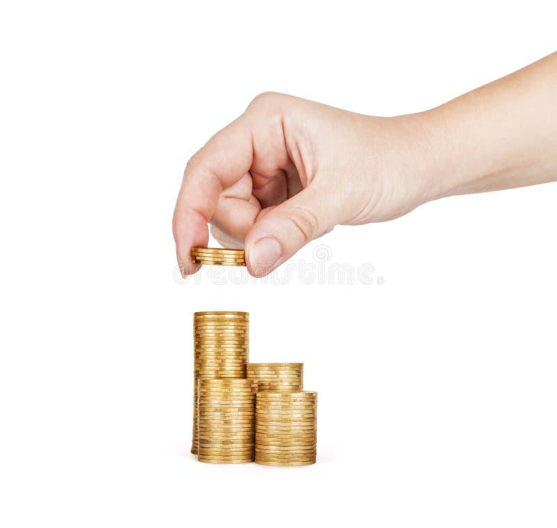 手投入了硬币对堆 库存图片