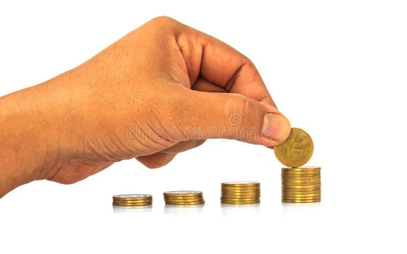 手投入硬币堆积在白色的硬币 库存照片