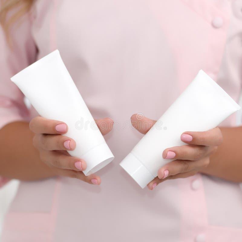 手护肤 拿着两支白色奶油色管反对在桃红色布料的身体,美好的美容师妇女手的女性手与 库存照片