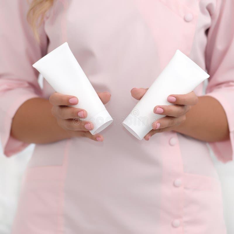 手护肤 拿着两支白色奶油色管反对在桃红色布料的身体,美好的美容师妇女手的女性手与 免版税库存图片