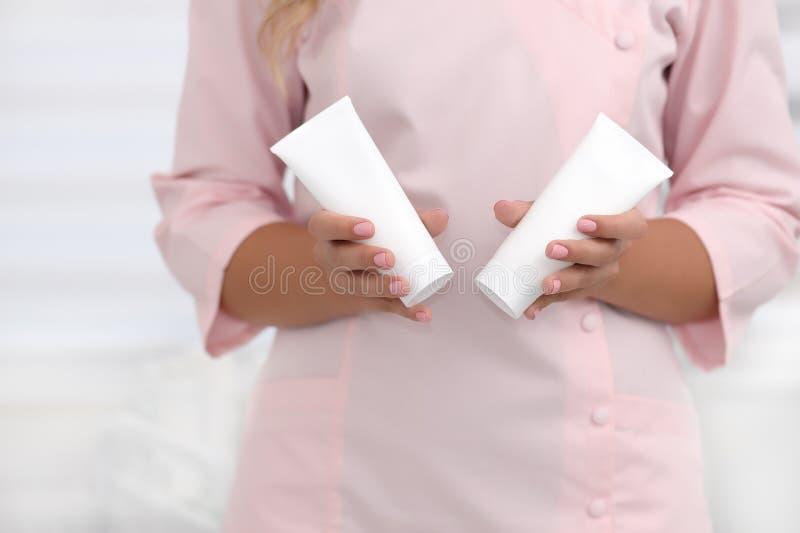 手护肤 拿着两支白色奶油色管反对在桃红色布料的身体,美好的美容师妇女手的女性手与 免版税库存照片