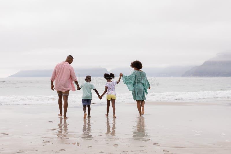 手拉手一起走在海滩的家庭 免版税库存图片