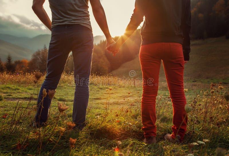手拉手两由秋季山的十几岁浪漫步行 免版税库存图片