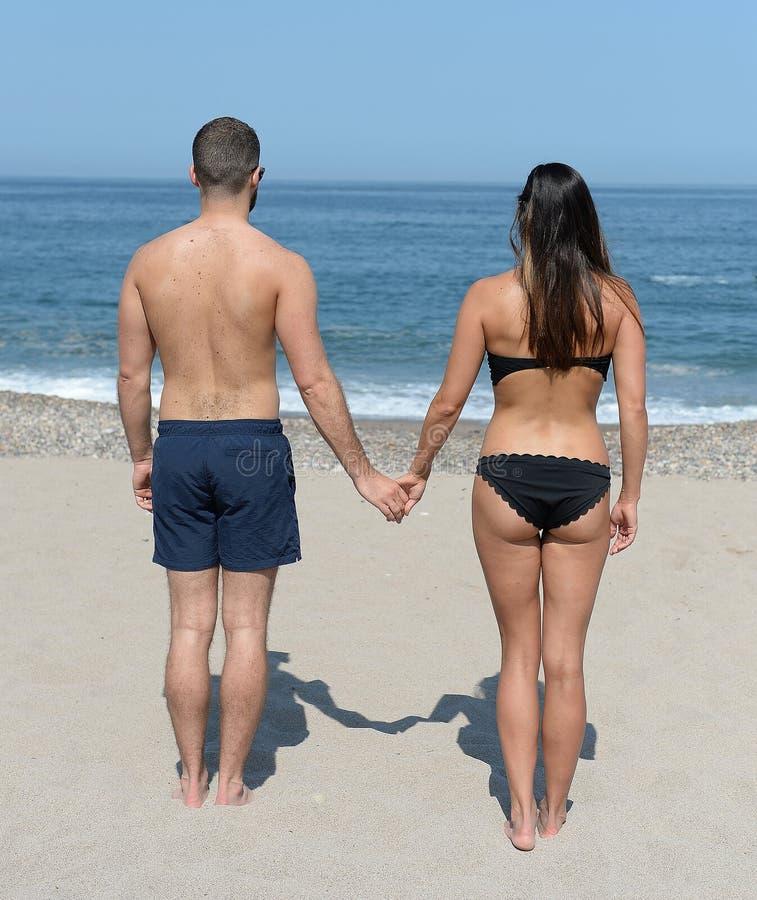 手拉手夫妇在海滩 免版税库存照片