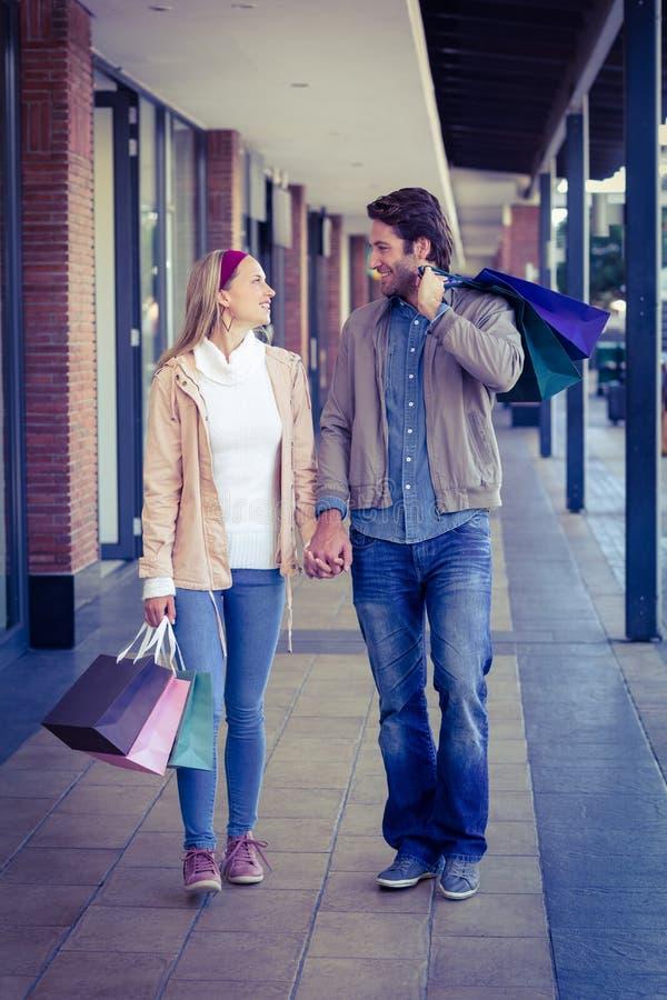 手拉手走与购物袋的微笑的夫妇 库存照片
