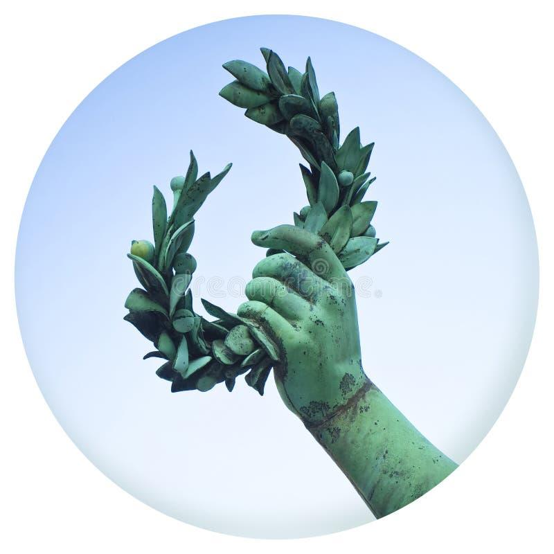 手拿着一个月桂树花圈-在色的背景的古铜色雕象-在圆的象形状-在a的摄影的成功和名望概念 免版税库存照片