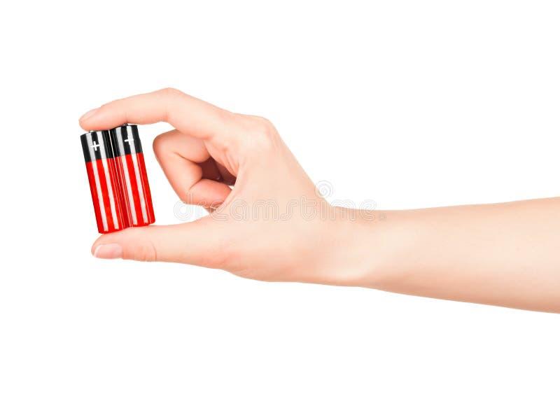 手拿着一个红色AA电池 库存图片