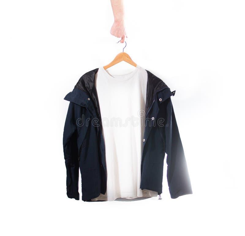 手拿着一件白色T恤杉和黑夹克在一个挂衣架在wh 免版税库存图片