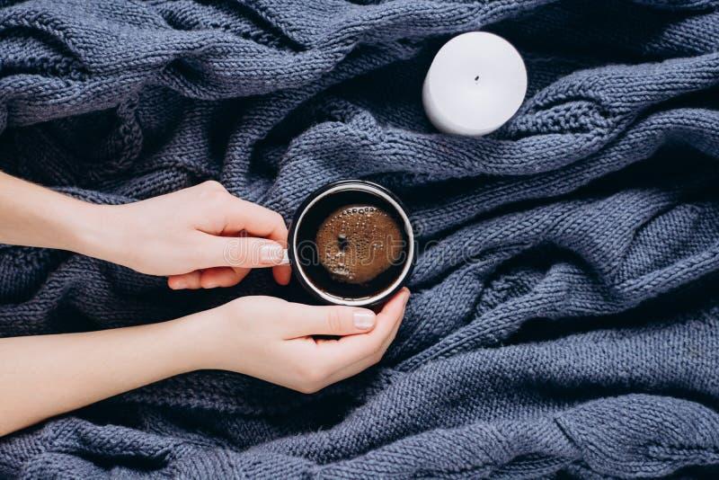 手拿着咖啡和蜡烛在蓝色被编织的毛线衣 平的位置,顶视图 库存照片