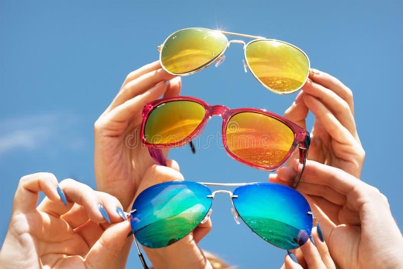 手拿着在天蓝色背景概念朋友的太阳镜 免版税图库摄影