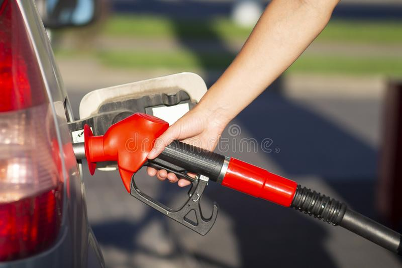 手拿着在汽油箱的汽油手枪在加油站特写镜头视图 免版税库存图片