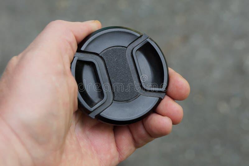 手拿着在灰色背景的一个黑塑料镜头盖 免版税图库摄影