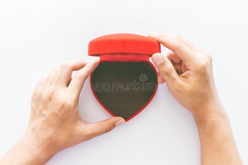 手拿着在白色的一个空的空白的红色心脏礼物盒 免版税库存照片