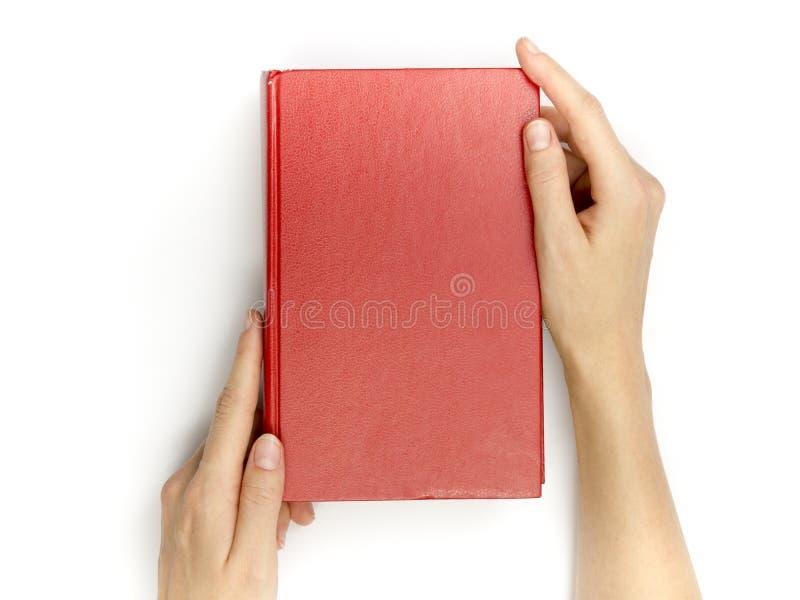 手拿着在白色的空白的红色精装书 图库摄影