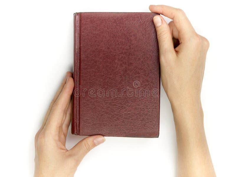 手拿着在白色背景的空白的红色精装书 库存照片
