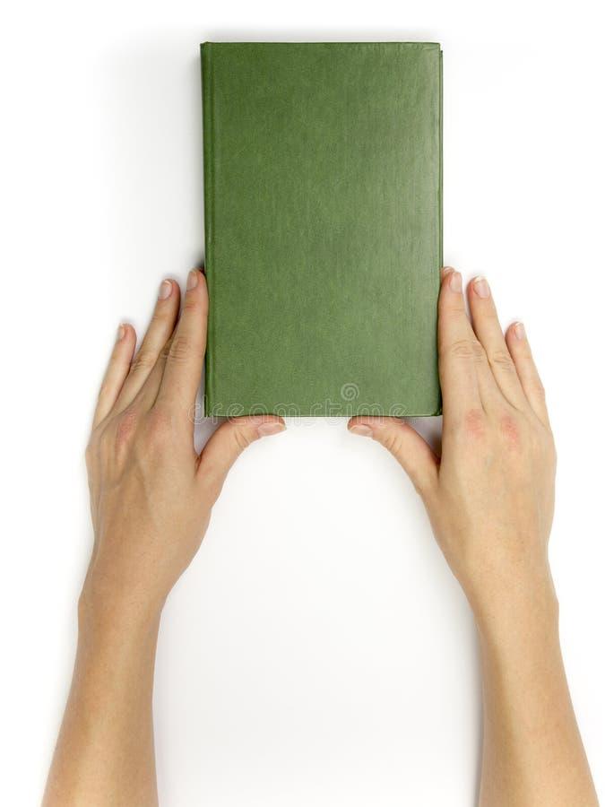 手拿着在白色背景的空白的红色精装书 免版税库存图片