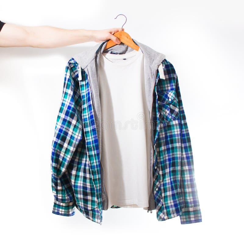 手拿着有格子花呢披肩蓝色衬衣的一件白色T恤杉在白色背景的一个挂衣架被隔绝 免版税库存图片
