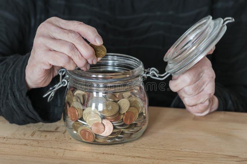 手拿着有零钱的一个金属螺盖玻璃瓶 免版税库存图片