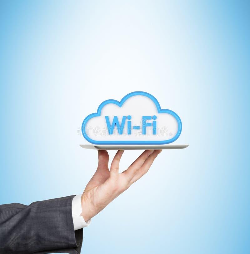 手拿着有Wi-Fi云彩的象的一种片剂 皇族释放例证