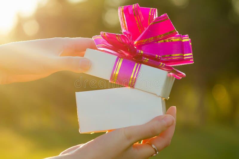 手拿礼物的粉色蝴蝶结打开的白色盒子 免版税库存照片