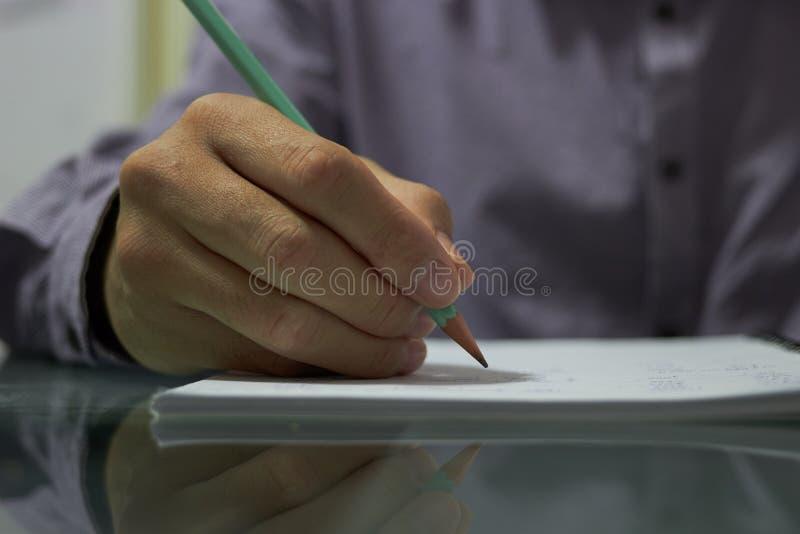 手持笔在笔记本纸上书写 库存图片