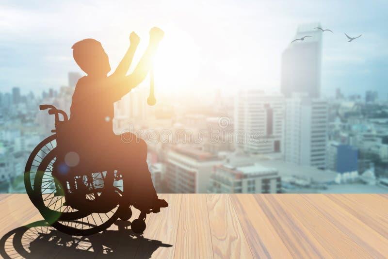 手持轮椅金牌顶的残疾人剪影获奖者,日落时间为城市背景 国际 免版税库存图片