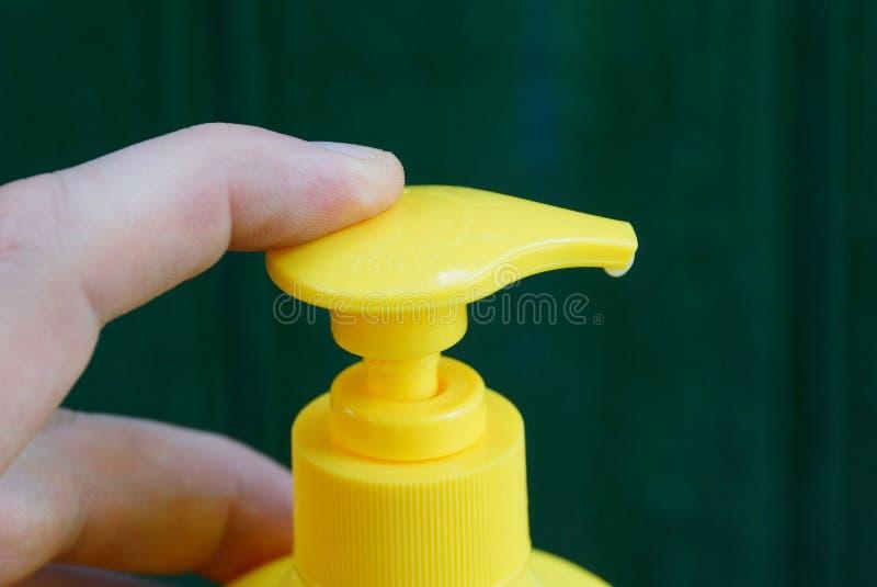 手指点击在瓶的一台黄色塑料分配器 免版税库存照片