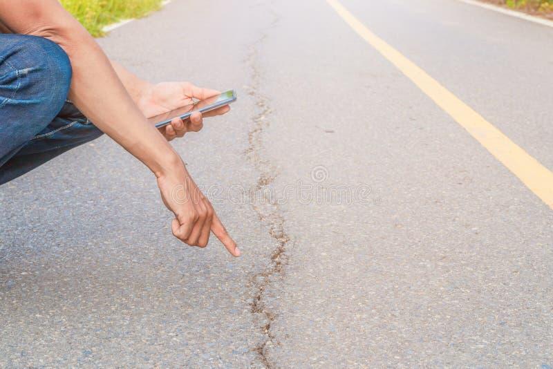 手指点和移动电话拍照片检查破裂的柏油路街道高速公路乡下 库存照片