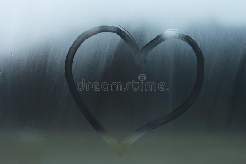手指的心脏在窗口被画冒汗了 心脏被绘在玻璃或在镜子 免版税库存照片