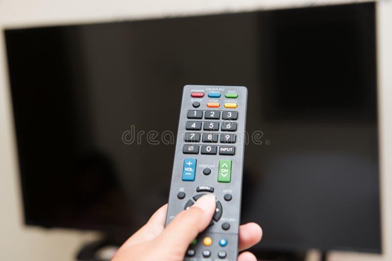 手按遥控打开电视 免版税库存照片