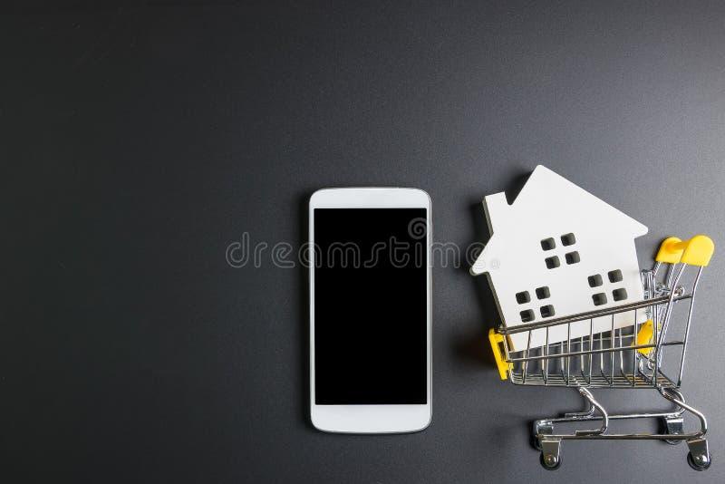 手推车、木水管模型和智能手机 E 不动产概念,新房概念 买房子 免版税库存照片