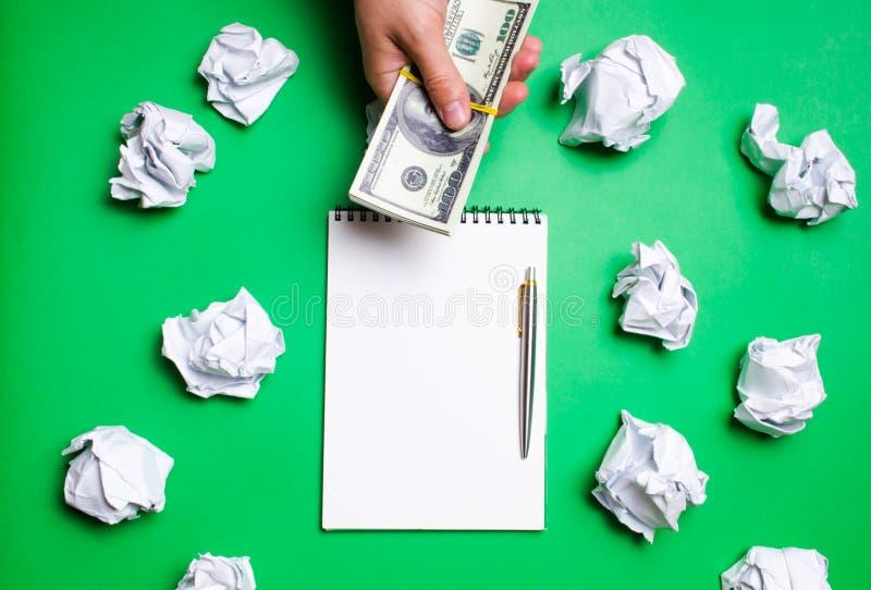 手提供金钱 有笔的白色笔记本在与纸球的绿色背景 买一个好想法的概念 T 免版税图库摄影