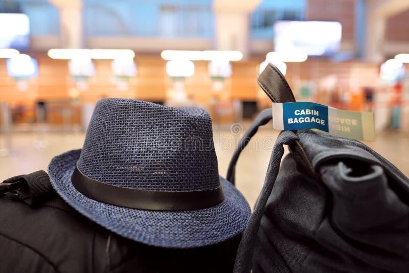手提行李和一个旅客` s帽子在一条长凳在机场 免版税库存照片