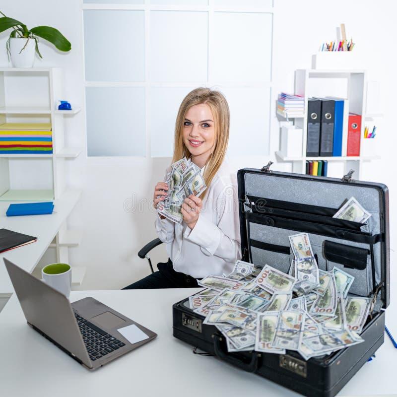 手握美元资金的女商人开心微笑破产经济金融理念 库存照片